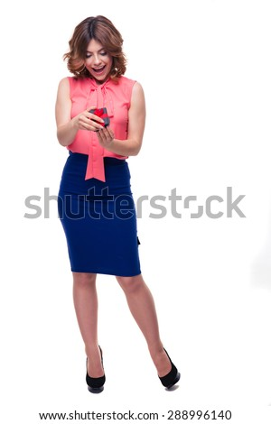 Full length portait of a happy casual woman opening gift box isolated on a white background - stock photo