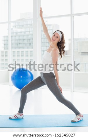 Full length portrait a fit young woman stretching hand in a bright fitness studio