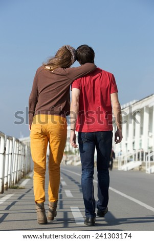 Full length portrait from behind of young man and woman walking outdoors - stock photo
