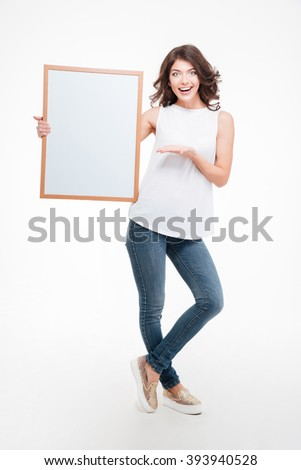Full length portrait o a cheerful woman holding blank board isolated on a white background - stock photo