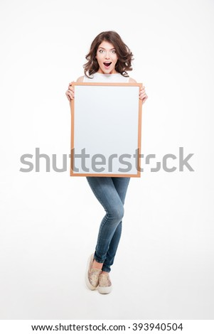 Full length portrait o a happy woman holding blank board isolated on a white background - stock photo