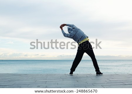 Full length portrait of a athletic man stretching in the morning and admiring beautiful view while  standing next to the sea - stock photo