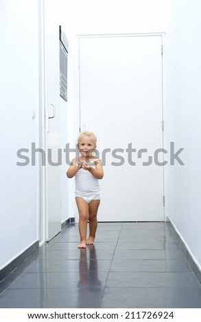 Full length portrait of a baby girl walking in hallway at home - stock photo