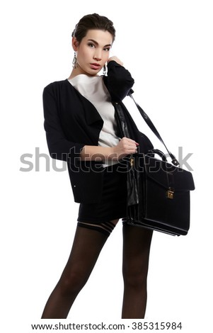 Full length portrait of a beautiful brunette in a business style, in suit and stockings with a briefcase on a gray background studio