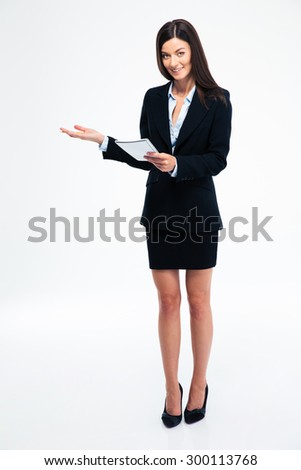 Full length portrait of a beautiful businesswoman holding notebook and showing welcome gesture isolated on a white background - stock photo