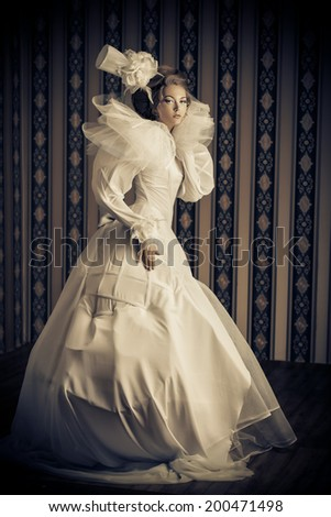 Full length portrait of a beautiful fashion model in the refined white dress and elegant hat. Vintage style. Art project.