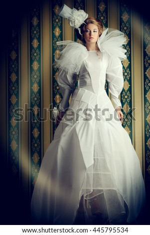 Full length portrait of a beautiful fashion model in the refined white dress and elegant hat. Vintage style. Art project. - stock photo