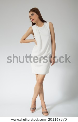 full length portrait of a beautiful fashion model wearing white dress, attractive india model standing against grey background. - stock photo