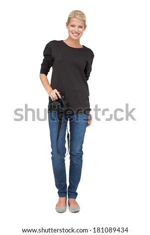Full length portrait of a beautiful female photographer over white background