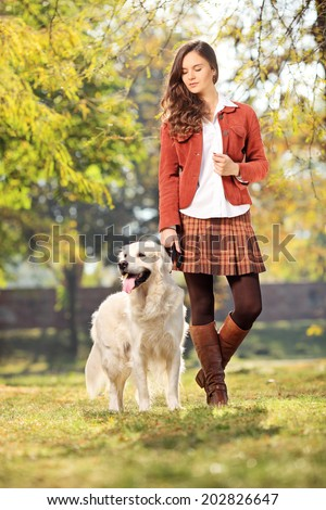 Full length portrait of a beautiful girl walking her dog in park