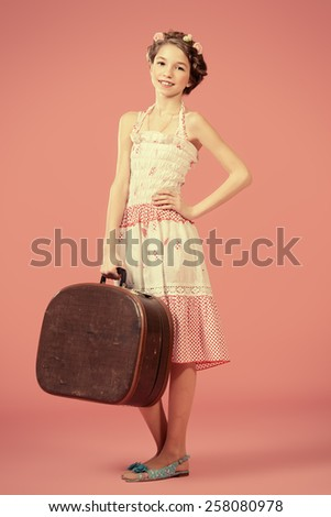 Full length portrait of a beautiful girl with braided hair wearing summer sundress. Children fashion.  - stock photo