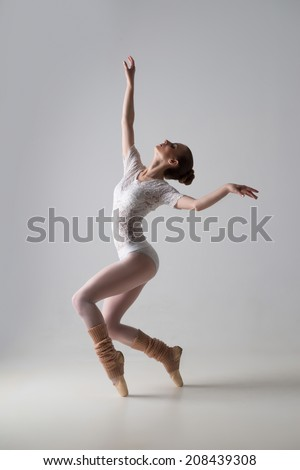Full length portrait of a beautiful graceful modern ballet dancer dancing isolated on grey background - stock photo