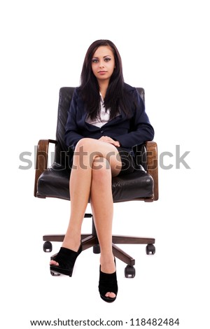 Full length portrait of a beautiful hispanic businesswoman sitting on an armchair isolated on white background - stock photo