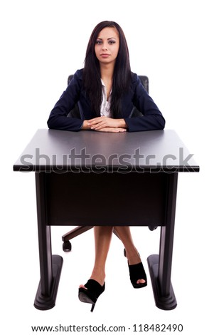 Full length portrait of a beautiful latin businesswoman sitting at desk isolated on white background - stock photo