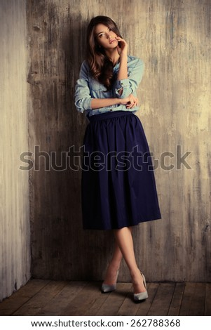 Full length portrait of a beautiful sensual woman in jeans clothes stands by the grunge wall. Fashion. - stock photo