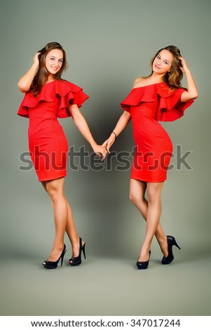 Full length portrait of a beautiful smiling twin sisters posing together in red dresses. Studio shot. Beauty, fashion. - stock photo