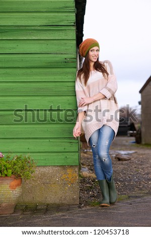 Full length portrait of a beautiful smiling young woman. She is wearing boots, hat, jeans and a big sweater. She is leaning against a green wall. Possible room for copy space - stock photo