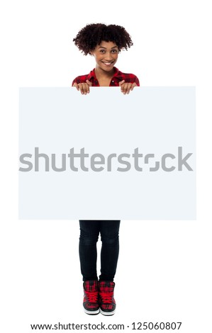 Full length portrait of a beautiful woman displaying blank white ad board.