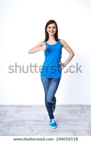Full length portrait of a beautiful woman gesturing thumb up - stock photo