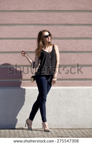 Full length portrait of a beautiful woman in dark blue jeans and black blouse on wall background - stock photo