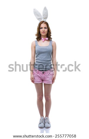 Full length portrait of a beautiful woman with bunny ears over white background - stock photo