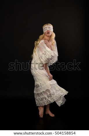 full length portrait of a beautiful woman with long blonde hair, wearing a white lace dress and a white blindfold, isolated against black studio background.