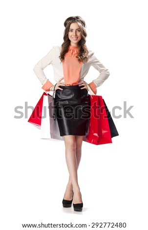 Full length portrait of a beautiful young brunette woman posing with shopping bags, isolated on white background - stock photo