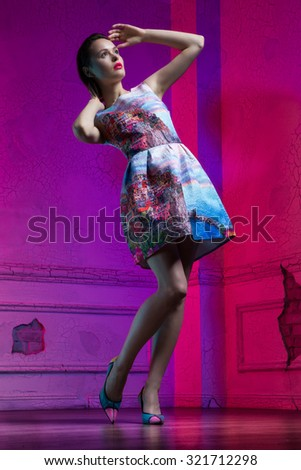 Full length portrait of a beautiful young girl wearing colorful dress and high heel shoes, with bright make up posing looking aside, standing in a purple room - stock photo