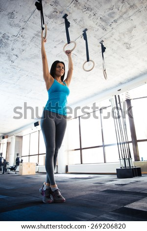 Full length portrait of a beautiful young woman doing exercise on gimnastic rings at gym - stock photo
