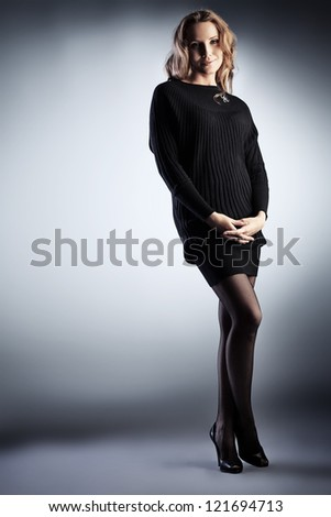 Full length portrait of a beautiful young woman in black dress.