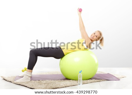 Full length portrait of a beautiful young woman lifting dumbbells while sitting on pilates ball.