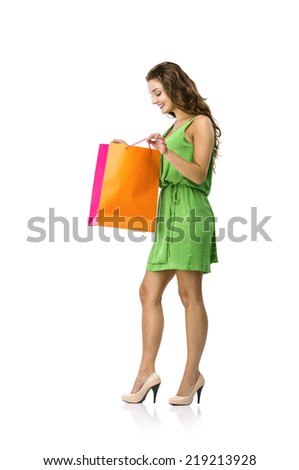 Full length portrait of a beautiful young woman posing with shopping bags, isolated on white background - stock photo
