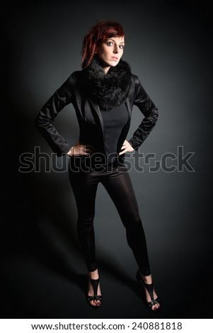 Full length portrait of a beautiful young woman with read hair wearing black blazer and fur in front of dark studio background