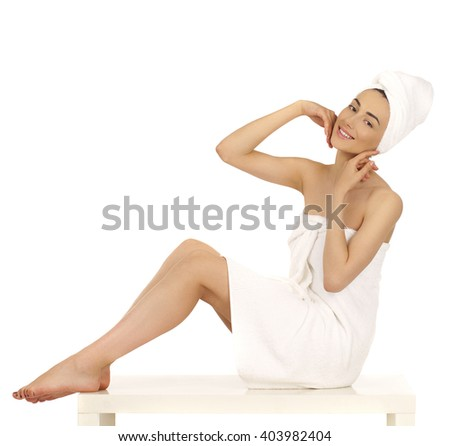 Full length portrait of a beautiful young woman wrapped towel isolated on white background