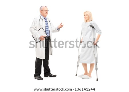 Full length portrait of a blond female patient in hospital gown with crutches and medical doctor during a conversation isolated on white background - stock photo