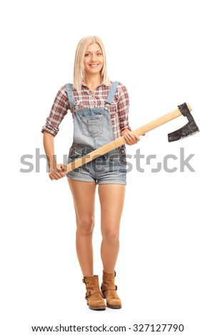 Full length portrait of a blond woman in jumpsuit and checkered shirt holding an axe and looking at the camera isolated on white background - stock photo
