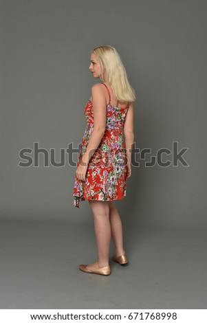 full length portrait of a blonde girl wearing red flower dress, standing pose against a grey background