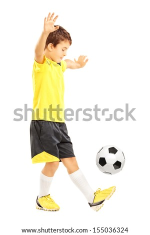 Full length portrait of a boy in sportswear joggling a soccer ball isolated on white background - stock photo
