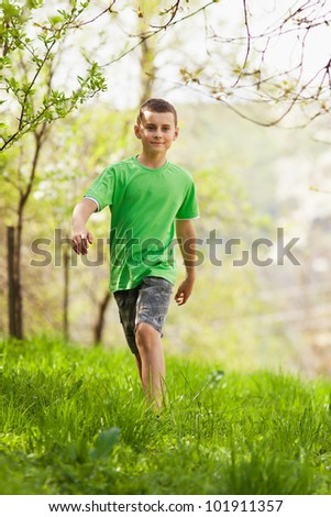 Full length portrait of a boy walking outdoor in a forest