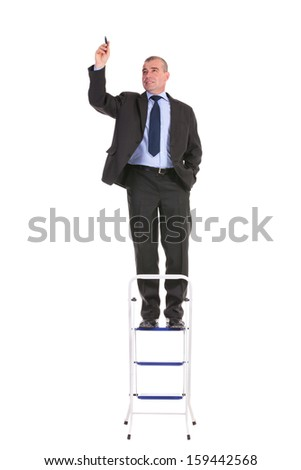 full length portrait of a business man standing on a ladder and writing while holding a hand in his pocket. on a white background - stock photo