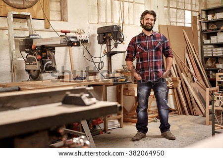 Full length portrait of a business owner who runs a carpentry studio, standing confidently with his hands in his pockets, smiling at the camera, in workshop with pieces of wood and woodwork machinery - stock photo