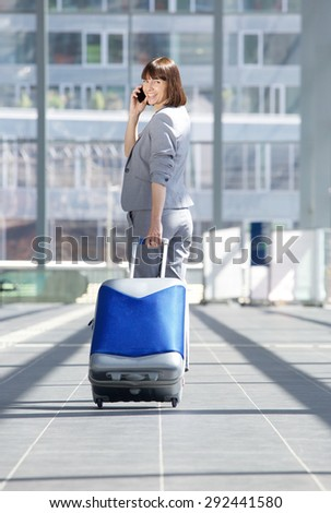 Full length portrait of a business woman walking away with travel bag and mobile phone - stock photo