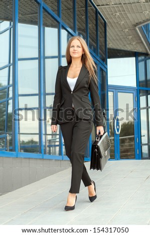 Full length portrait of a business woman walking with briefcase at office building