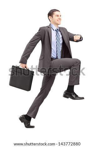 Full length portrait of a businessman doing a huge step towards isolated on white background - stock photo