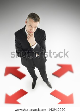 Full length portrait of a businessman in centre of four arrows against gray background - stock photo