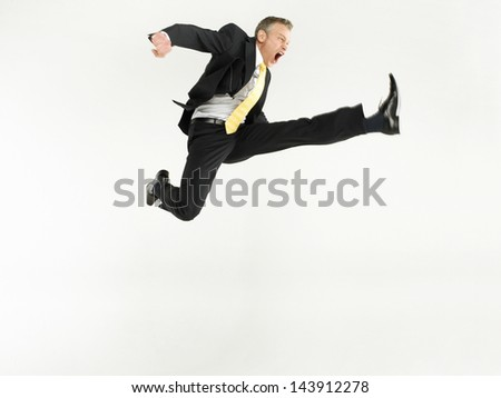 Full length portrait of a businessman jumping against white background - stock photo
