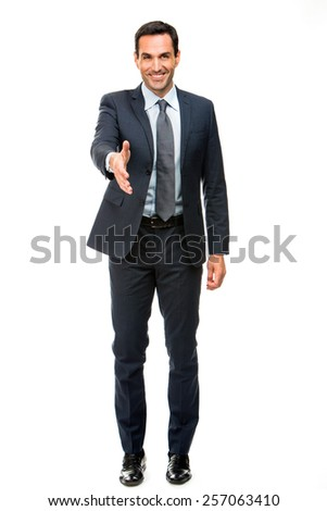 Full length portrait of a businessman smiling raising his arm for shaking hands - stock photo