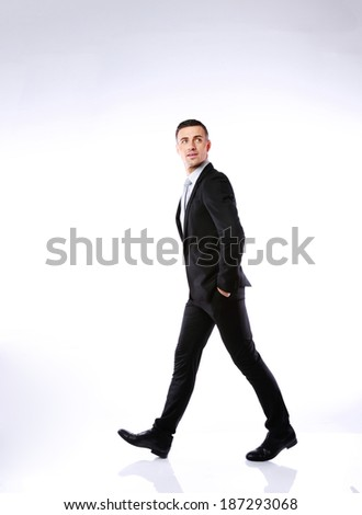 Full length portrait of a businessman walking on gray background - stock photo