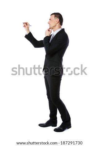 Full-length portrait of a businessman writes with pen at copyspace over white background - stock photo