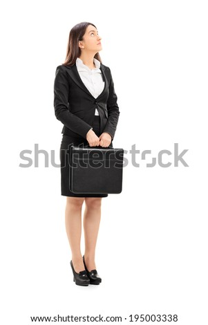 Full length portrait of a businesswoman holding a briefcase and looking up isolated on white background - stock photo